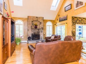 the soaring atrium family room (highlighted by stone fireplace, radius windows and double skylights)